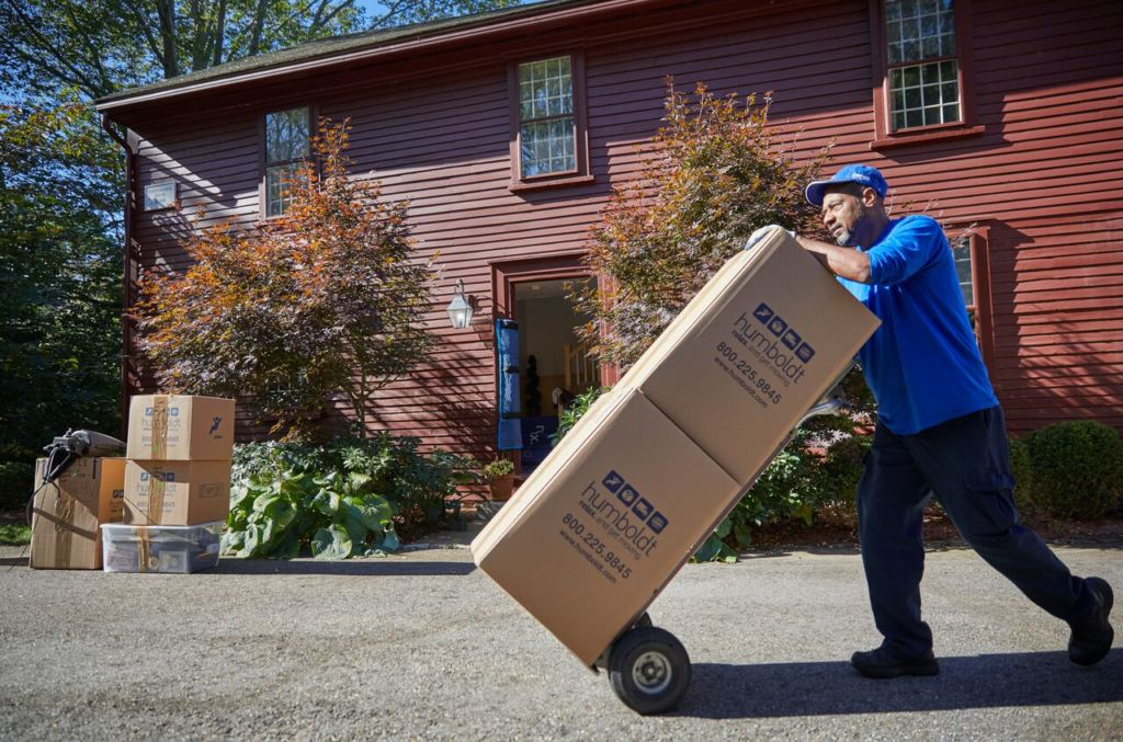 Movers moving boxes on a dolly